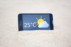 Smart phone with weather forecast on screen in sand Royalty Free Stock Image