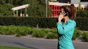 Smart phone woman calling on mobile phone at park. Handsome young woman talking on smartphone smiling happy outdoors. waiting. stock video footage