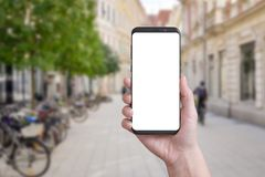 Smart phone in woman hand on city streets Stock Photography