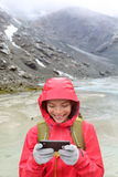 Smart phone woman texting using app on smartphone. Smart phone woman texting sms using app on smartphone with touchscreen gloves. Happy hiker with mobile phone Royalty Free Stock Photo