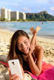 Smart phone woman using smartphone app on beach Royalty Free Stock Images