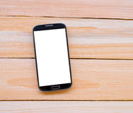 Smart phone on wooden desk.  Royalty Free Stock Images