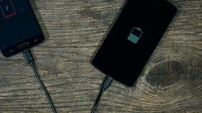 Smart phones charging on grunge wood background. Status on screen. stock video