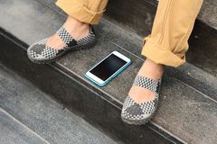 Smart phones place beside shoes at the park Stock Photos