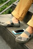 Smart phones place beside shoes at the park Royalty Free Stock Photos