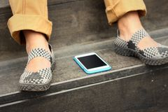 Smart phones place beside shoes at the park Royalty Free Stock Image