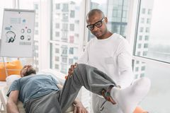 Smart physical therapist lifting his patients leg. Physical rehabilitation. Smart physical therapist standing near his patient while lifting his leg Stock Photos
