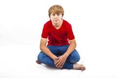 Smart pojke med rött skjortasammanträde fotografering för bildbyråer