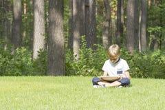 Smart pojke som utomhus använder en minnestavla Tillfällig kläder Teknologi livsstil, utbildning, folkbegrepp Fotografering för Bildbyråer