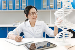 Smart positive woman writing down the research results. Scientific report. Smart nice positive woman sitting at the table and looking at the gene model while Royalty Free Stock Image