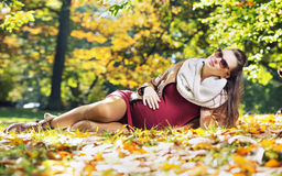 Smart pregnant woman in the autumn park Stock Photo