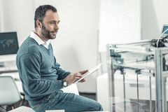 Smart professional adult engineer using a tablet. Digital device. Smart professional engineer using a tablet while being in the office royalty free stock photo