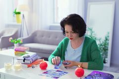 Smart professional fortune teller interpreting the meanings of cards. Difficult job. Smart professional fortune teller looking at the cards while interpreting stock images