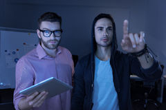 Smart professional IT men working with innovative technologies. Technological progress. Smart professional brutal men standing in the middle of the office and Royalty Free Stock Photos