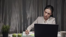 Young freelancer woman working at home office. Smart and professional young freelancer woman in formal wear clothes working at home office, sitting behind table stock video footage