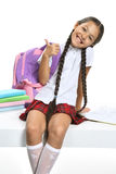 Smart pupil. Little Asian beautiful girl in school uniform sitting on white Royalty Free Stock Image