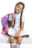 Smart pupil. Little Asian beautiful girl in school uniform sitting on white royalty free stock photo