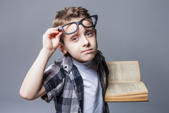 Smart pupil in glasses with textbook in hands Royalty Free Stock Photography