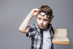 Smart pupil in glasses with textbook in hands Stock Images