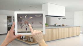 Smart remote home control system on a digital tablet. Device with app icons. Interior of professional modern wooden kitchen. With accessories in the background stock images