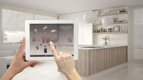 Smart remote home control system on a digital tablet. Device with app icons. Modern kitchen with shelves and cabinets in the. Background, architecture interior stock image