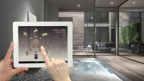 Free Smart Remote Home Control System On A Digital Tablet. Device With App Icons. Interior Of Minimalist House In The Background, Archi Stock Images - 113933854