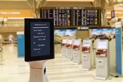Smart robotic technology concept, The passenger follow a service robot to a counter check in in airport, the robot can help and gi. Ve some information to royalty free stock image