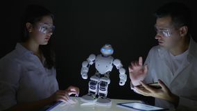 Smart robotic technology, Electronics engineers collaborating researching abilities of automated robot in modern lab
