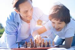 Proud father watching son playing chess stock photography