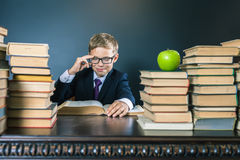 Smart school boy reading a book at library Stock Photography