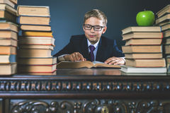 Smart school boy reading a book at library Stock Image