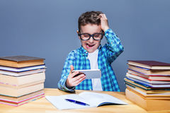 Smart schoolboy doing homework with tablet pc Stock Photography