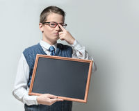 Smart schoolboy in glasses with empty chalkboard Royalty Free Stock Photo