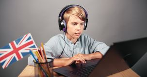 Boy on online English lesson. Smart schoolboy having online english lesson online, modern technologies in distant education, technologies stock footage