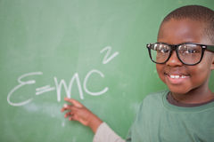Smart schoolboy showing the mass-energy equivalence Royalty Free Stock Photo