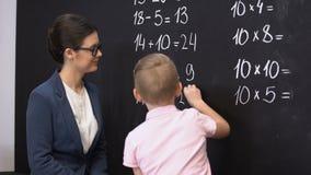 Smart schoolboy solving math exercises on blackboard, teacher standing near. Stock footage stock video