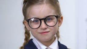 Smart schoolgirl adjusting eyeglasses closeup, elementary school pupil education. Stock footage stock video footage