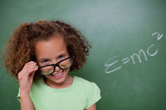Smart schoolgirl looking above her glasses Royalty Free Stock Photo