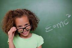 Smart schoolgirl looking above her glasses Royalty Free Stock Photo