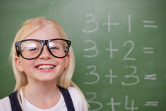 Smart schoolgirl posing in front of a blackboard Royalty Free Stock Photography