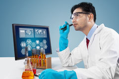 Smart scientist thinks an idea. Male scientist working in the laboratory with chemical fluid and thinks about discovery Stock Image