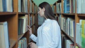 Smart se och härlig ung flicka i den vita skjortan och exponeringsglas i collageskolaarkivet som väljer boken att läsa arkivfilmer