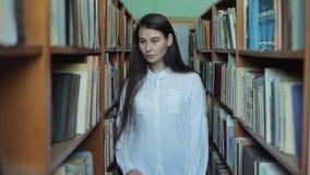 Smart se och härlig ung flicka i den vita skjortan och exponeringsglas i collageskolaarkivet som väljer boken att läsa lager videofilmer