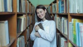 Smart se och härlig ung flicka i den vita skjortan och exponeringsglas i collageskolaarkivet som väljer boken att läsa stock video