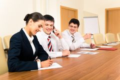 Smart secretary. Photo of confident businessmen looking at pretty secretary during meeting in the office Royalty Free Stock Images