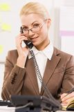 Smart secretary. Portrait of helpful secretary speaking on the phone with a client Royalty Free Stock Image
