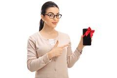 Smart seende kvinna som visar en telefon som slås in med det röda bandet arkivbild