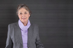 Smart senior woman with grey hair on grey background Royalty Free Stock Image