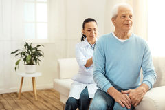 Smart serious doctor sitting behind her patient Stock Image