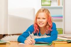 Smart sido menina loura faz trabalhos de casa no assoalho home Fotografia de Stock